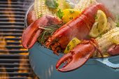 stock photo of lobster tail  - Steamed lobster and vegetables in a hot steaming pot on a barbecue grill - JPG