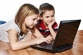 picture of fanny  - Sister and brother looking to laptop lying on the floor - JPG