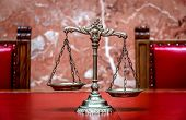 stock photo of justice law  - Symbol of law and justice on the red table law and justice concept focus on the scales - JPG
