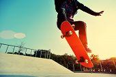 stock photo of skateboard  - young skateboarder legs skateboarding at outdoor skatepark - JPG
