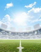 stock photo of football pitch  - A soccer stadium with a marked green grass pitch in the daytime under a blue sky - JPG