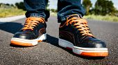 stock photo of tar  - A person walking on orange black sport shoes on a tarred road - JPG