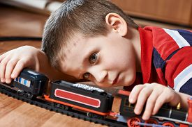 image of track home  - Little boy playing with railway lying on the floor - JPG