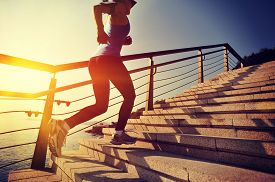 stock photo of athletic woman  - healthy lifestyle sports woman running up on stone stairs sunrise seaside - JPG