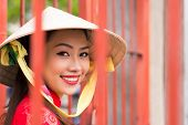 stock photo of conic  - Portrait of charming Vietnamese girl wearing traditional conical hat - JPG