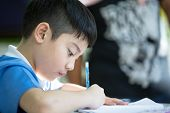 picture of homework  - Young asian boy doing his homework  - JPG