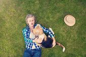 picture of beautiful senior woman  - Beautiful senior woman with a dog lying on a grass - JPG