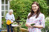 picture of granddaughters  - Portrait Of Teenage Granddaughter Helping Grandmother In Garden - JPG