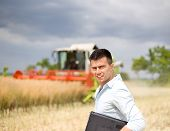 picture of harvest  - Young attractive farmer carrying laptop in the field during rapeseed harvest - JPG