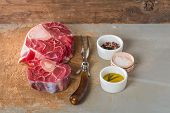 stock photo of veal  - Raw fresh cross cut veal shank and seasonings for making Osso Buco on wooden background - JPG