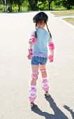 stock photo of roller-skating  - Cute smiling little girl in pink roller skates and protective gear outdoor - JPG