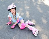 image of roller-skating  - Cute smiling little girl in pink roller skates and protective gear outdoor - JPG