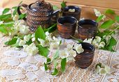 stock photo of teapot  - Teapot with small cups and jasmine flowers - JPG