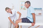 picture of knee  - Doctor examining her patient knee in medical office - JPG