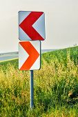 stock photo of curves  - Road curve warning signs on steep curve turn - JPG