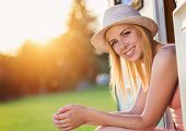 image of campervan  - Beautiful young woman sitting in a camper van on a summer day - JPG