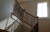 picture of bannister  - Sunlight from an open window with blinds shines onto stairway creating diagonal lines on wall - JPG