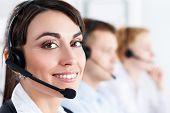 stock photo of helpdesk  - Three call center service operators at work - JPG