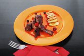 image of black-cherry  - grilled beef meat with berries fried potatoes and cherry under sweet honey sauce on orange plate over black wooden table - JPG