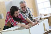 stock photo of senior class  - Young woman with senior craftsman in carpentry class - JPG
