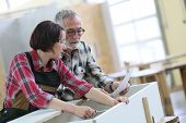 foto of carpentry  - Young woman with senior craftsman in carpentry class - JPG