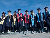 image of graduation  - young graduates students group  standing in front of university building on graduation day - JPG