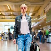 stock photo of board-walk  - Casually dressed young stylish female traveller walking the airport terminal hall   draging suitcase and a handbag behind her - JPG