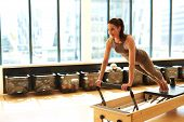 stock photo of leotard  - Healthy Smiling Brunette Woman Wearing Leotard and Practicing Pilates in Exercise Studio - JPG