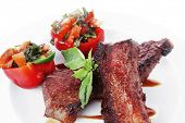 pic of braai  - fresh red beef meat steak barbecue garnished vegetable salad and basil  in half of pepper bell on white plate isolated over white background - JPG