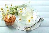 stock photo of chamomile  - Cup of chamomile tea with chamomile flowers and tasty muffin on color wooden background - JPG
