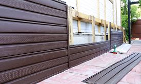 picture of soffit  - Installation of brown plastic siding on the facade of the house - JPG