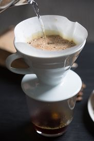 picture of boil  - Preparing coffee in a manual filter pouring boiling water onto the freshly ground coffee beans close up view of the water and frothy surface of the coffee - JPG
