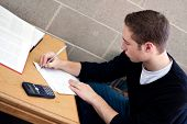 foto of midterm  - A young high school or college student working on his math homework - JPG