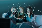 Teenage girls watching horror movie with popcorn poster