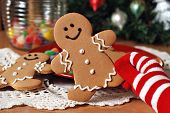Holiday still life of colorful gloved hand holding a gingerbread man cookie.  Gumdrops and christmas