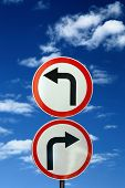 two opposite road signs against blue sky and clouds 2