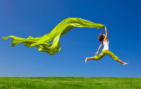 foto of landscapes beautiful  - Beautiful young woman jumping on  a green meadow with a colored tissue - JPG