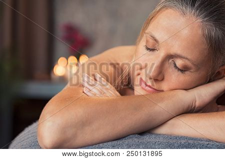 poster of Closeup face of mature woman lying on a massage table with eyes closed in a wellness center. Blonde