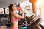 Slim Pretty Joyful Girl Jogging At The Treadmill And Drinking A Shaker With Protein Cocktail In The  poster