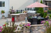 Upscale Outdoor Patio With Kitchen Area And Comfortable Wicker Furniture In The Shade Of A Striped U poster
