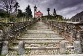 Long Stairs Leading Up To An Old Rose Colored Church Under An Expressive Overcast Sky poster