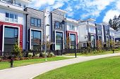 Beautiful new contempory suburban attached townhomes with colorful summer gardens in a Canadian neig poster