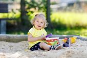Cute Toddler Girl Playing In Sand On Outdoor Playground. Beautiful Baby In Red Gum Trousers Having F poster