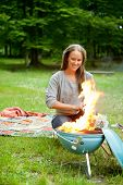 Beautiful young woman sitting in front of flaming portable barbecue at an outdoor picnic