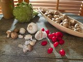 picture of crimini mushroom  - Garlic with cherry tomatoes crimini mushrooms and an artichoke by kitchen window - JPG