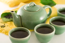stock photo of black tea  - teapot and four cups filled with green tea - JPG