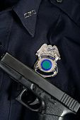 stock photo of glock  - Handgun laying on blue police uniform with badge - JPG