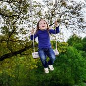 stock photo of seesaw  - Cute little girl swinging on seesaw to the sky