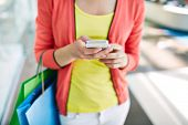 stock photo of mall  - Female customer with cellular phone and shopping bags in the mall - JPG