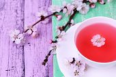 picture of stimulating  - Fragrant tea with flowering branches on wooden table close - JPG